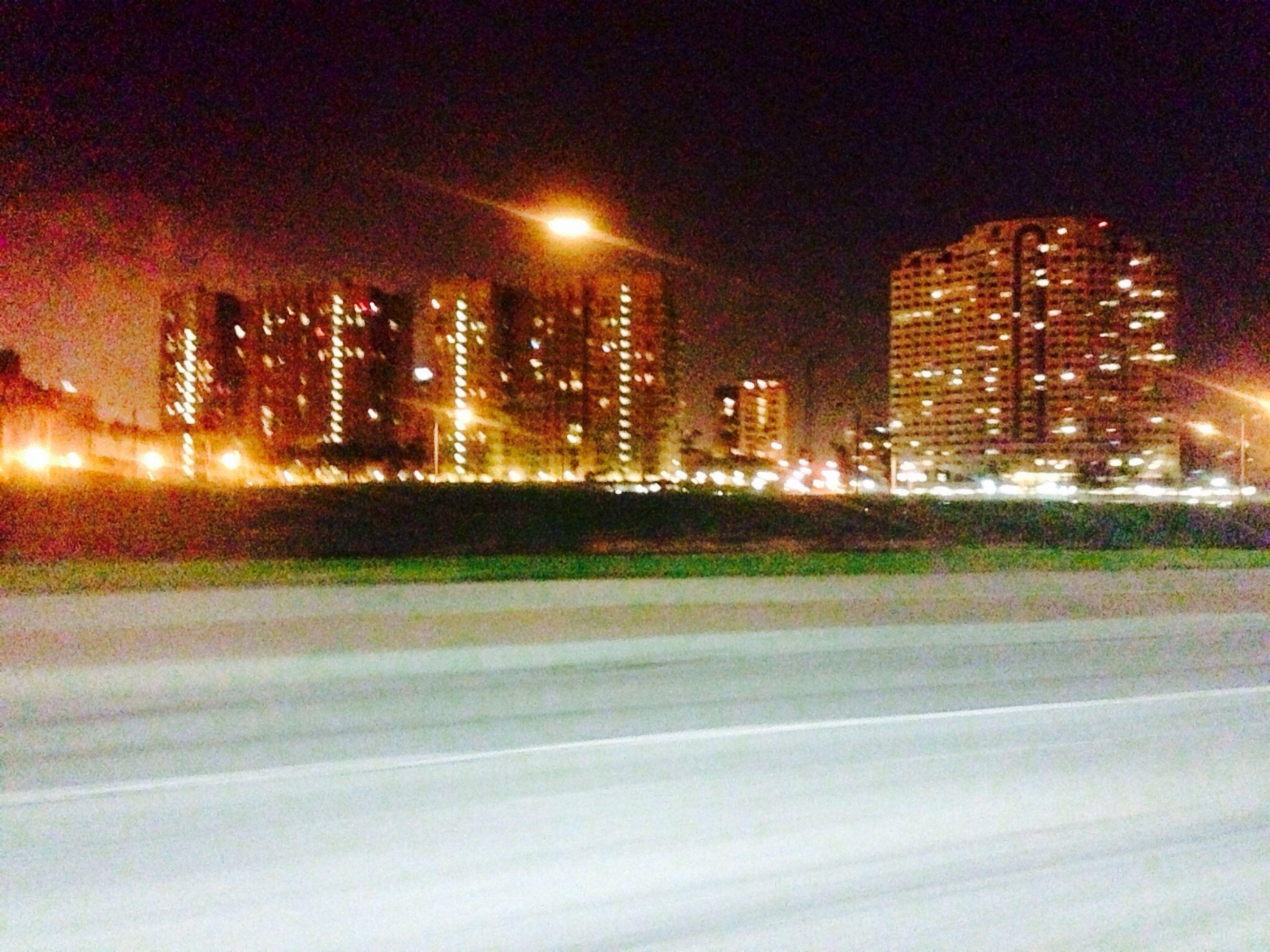 illuminated, building exterior, city, night, architecture, built structure, skyscraper, modern, street light, office building, cityscape, street, road, tall - high, transportation, city life, urban skyline, city street, tower, building