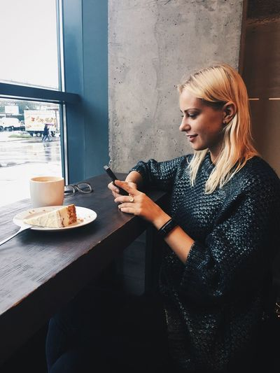 Young woman having cake and coffee