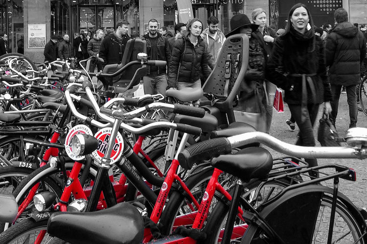 street photography bicycles and tourists in Amsterdam Amsterdam Bicycles Of Amsterdam Black And Red Black And White With A Splash Of Colour City Life In A Row Tourism Transportation Up Close Street Photography Up Close Street Photograpy Up Close With Street Photography