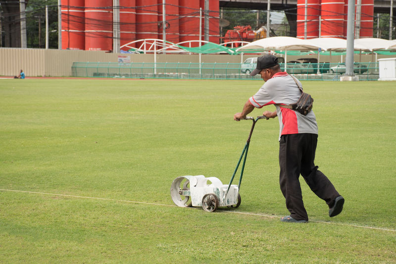 Rear view of man with dog on field