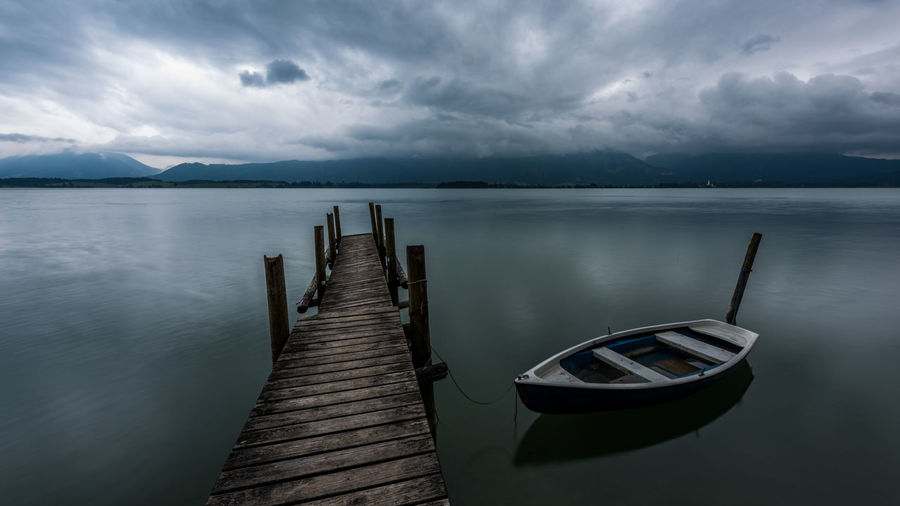 Boat moored by wooden pier in lake against cloudy sky