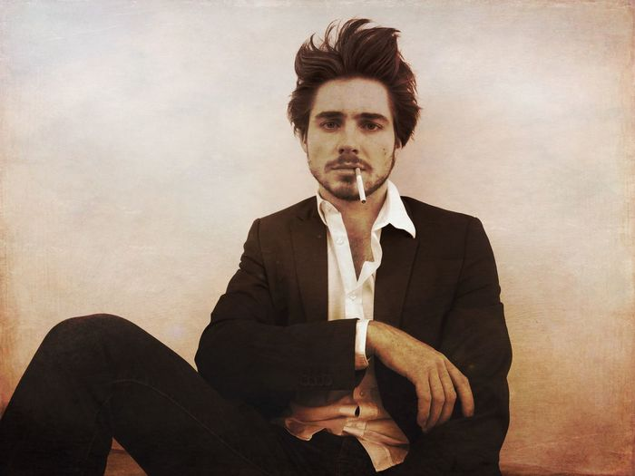 Portrait of young man smoking cigarette while sitting against wall