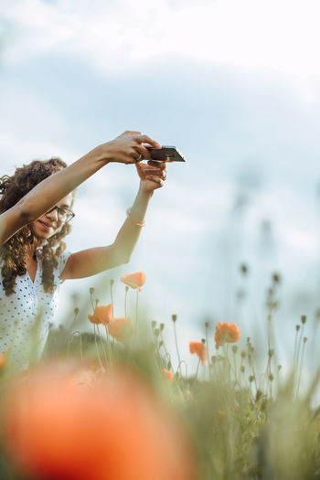 Woman photographing flowering plants against sky