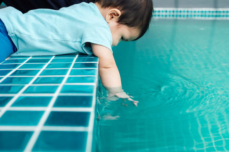 Side view of baby girl sitting by swimming pool