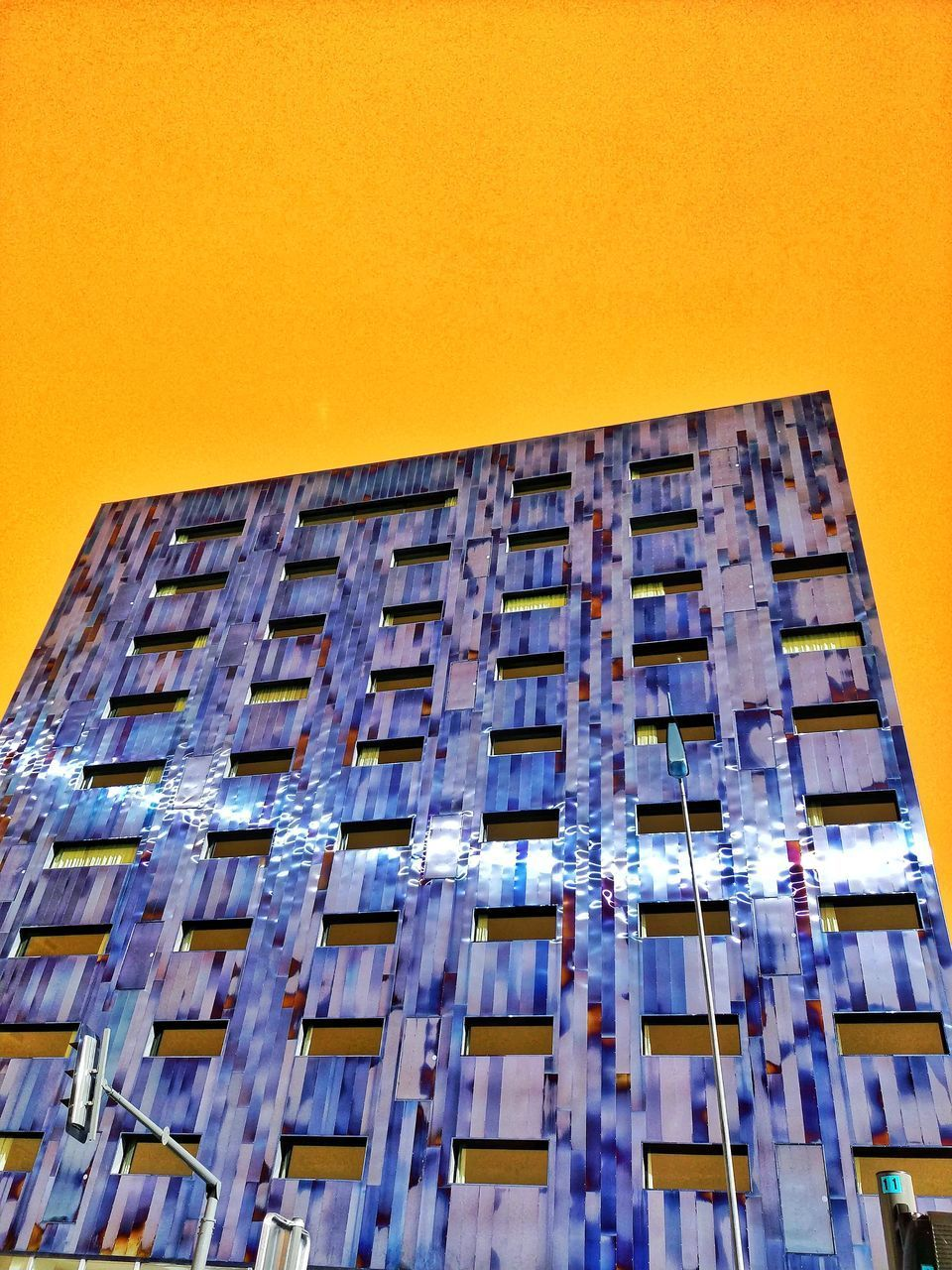 building exterior, architecture, built structure, low angle view, sky, window, no people, building, clear sky, sunset, city, yellow, nature, outdoors, copy space, orange color, blue, day, modern, residential district, apartment