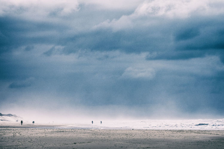Few scattered people on the beach of the atlantic ocean on an overcast and foggy day