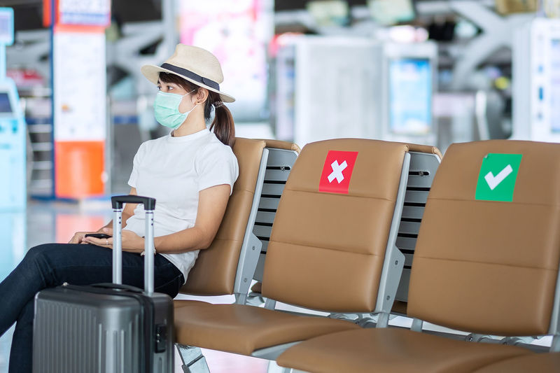 Woman wearing mask with luggage sitting in airport
