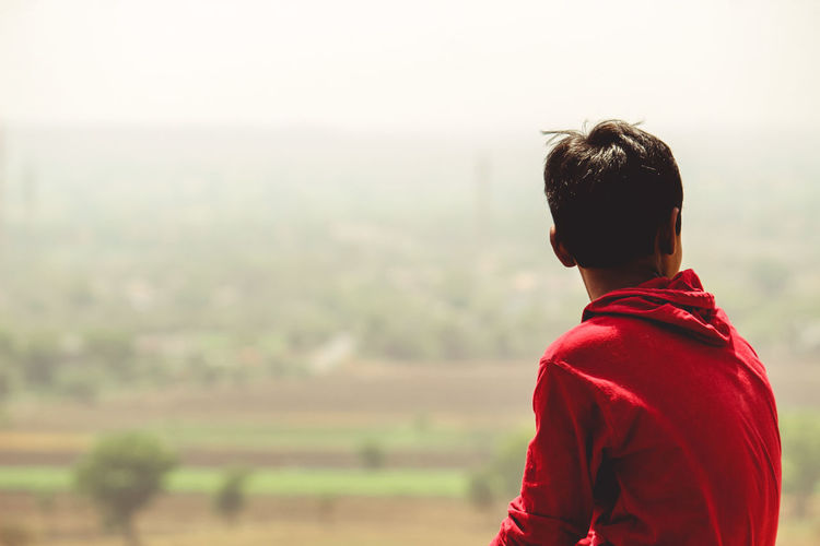 Boy Sitting Against Landscape During Foggy Weather