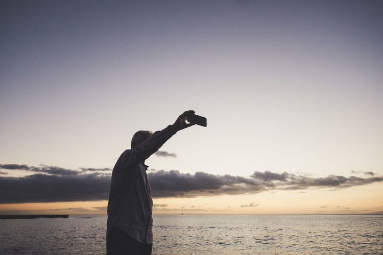 Man photographing from mobile phone at beach during sunset