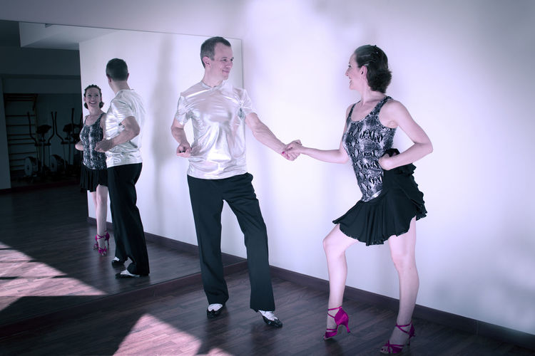 Full length of couple dancing against mirror