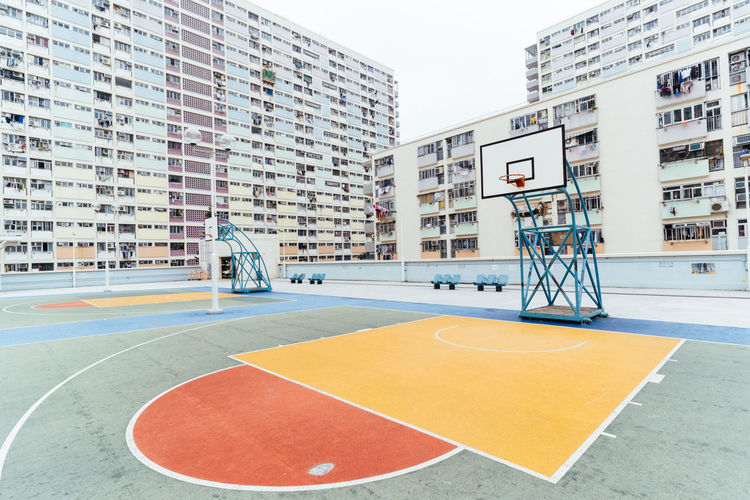 View of basketball court against buildings in city