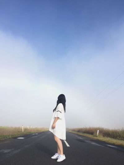 Side view of woman standing on country road against sky