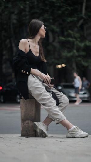 Woman sitting on street in city