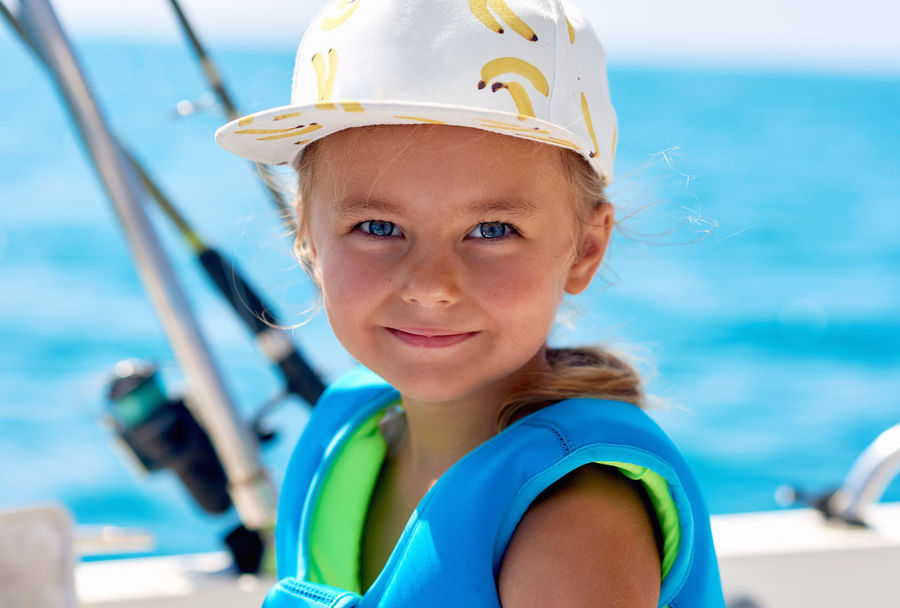 Lovely little girl with a fishing rod fishing on the boat 5 Years Old Beautiful Girl Bright Colors Fishing Rod Happy Looking At Camera Positive Recreational Boat Summertime Sunlight Cheerful Fishing Fishing Boat Hobbies Leisure Activity Little Girl One Person Real People Recreational Pursuit Sea Smiling Summer Sunny Day Water
