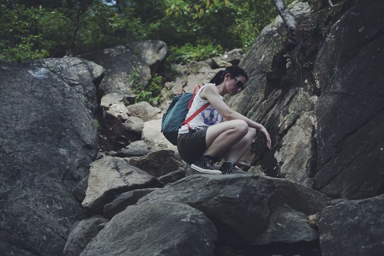 Low Angle View Of Woman Crouching On Rock