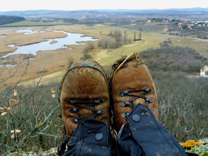 Low section of male hiker wearing dirty shoes on cliff against landscape