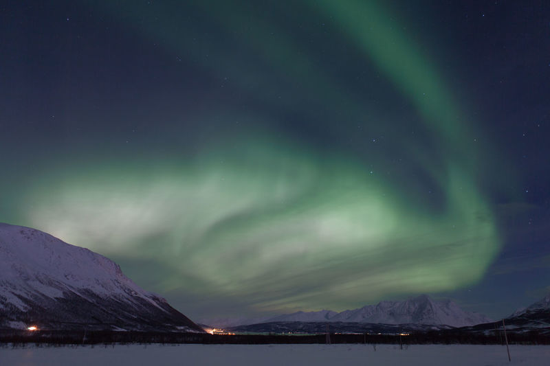 Aurora Borealis Over Snowcapped Mountains At Night