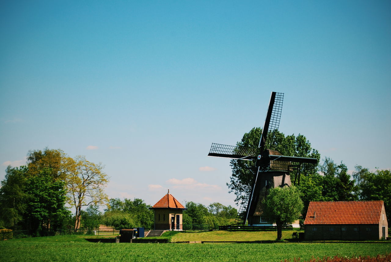 Traditional windmill on grassy field against clear sky