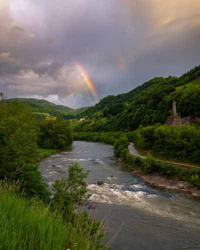 Scenic view of rainbow over river against sky
