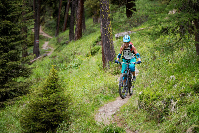 Woman riding bicycle at forest
