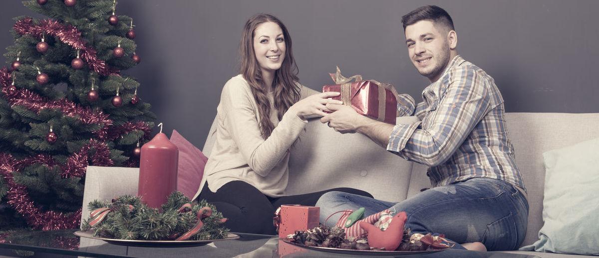 Woman giving gift to man during christmas