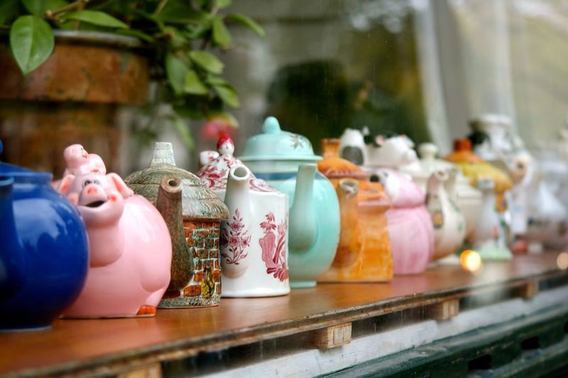 Close-up of teapots on rack at store