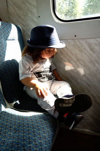 It's About The Journey Kidsphotography Train Hat One Person Real People Sitting Casual Clothing Clothing Lifestyles Day Cap Leisure Activity Full Length Sunlight High Angle View Indoors  Three Quarter Length Men Relaxation Seat Holding
