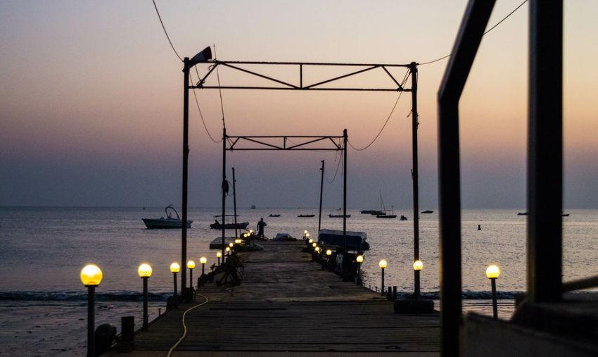 Illuminated Pier On Sea Against Sky During Sunset