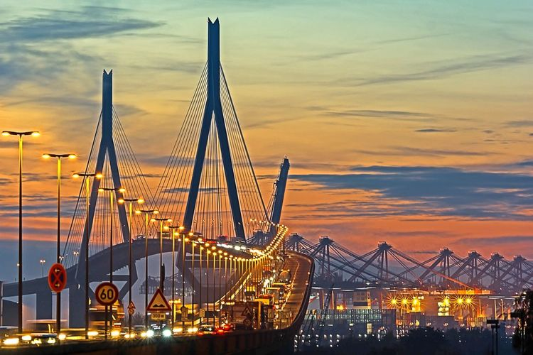 Cars moving on illuminated kohlbrand bridge against cloudy sky during sunset