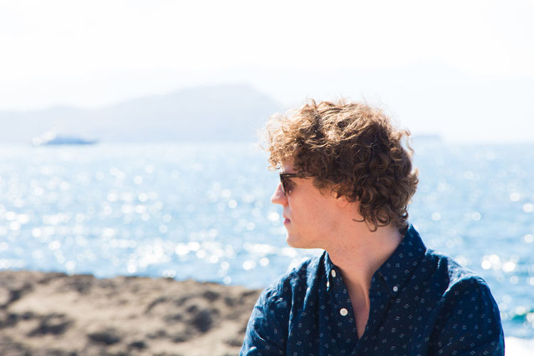 Young man with curly hair against sea on sunny day