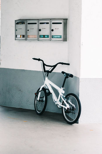 Bicycle parked against wall of building