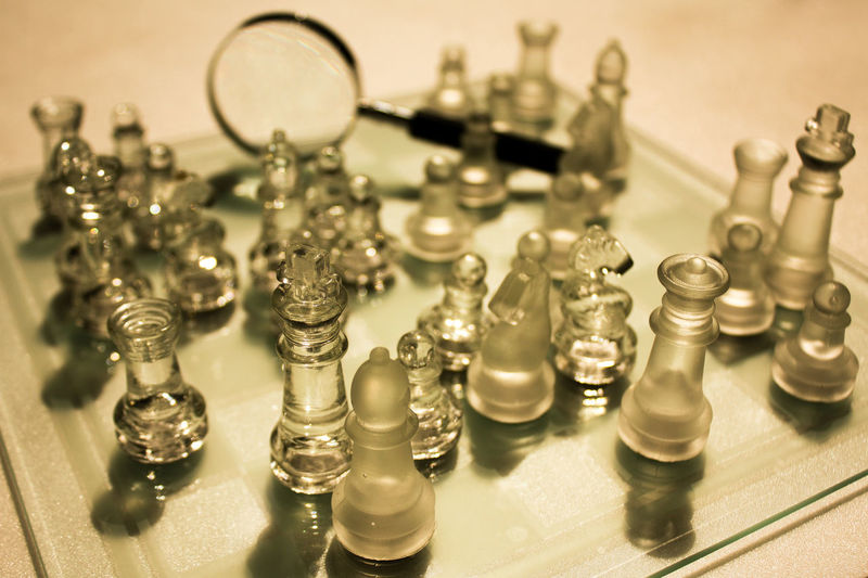 High angle view of glass chess pieces on board