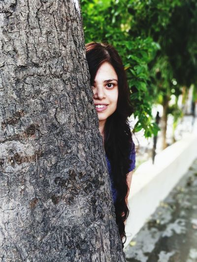 Portrait Of Smiling Young Woman Looking From Behind Tree Trunk