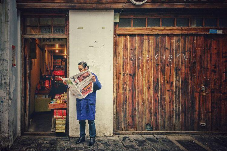 Man Reading Newspaper Outside Shop
