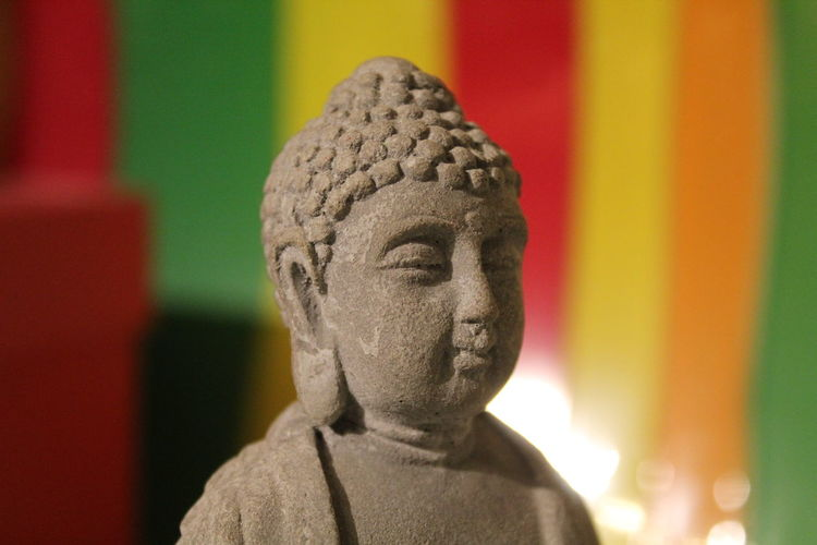 Close-up of buddha statue in sunny day