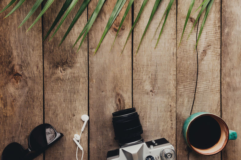 Flat lay travel concept, photo camera, cup of coffee, eyeglasses and earphones, palm leaf