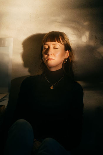 Portrait of a young woman with her eyes closed sitting against wall