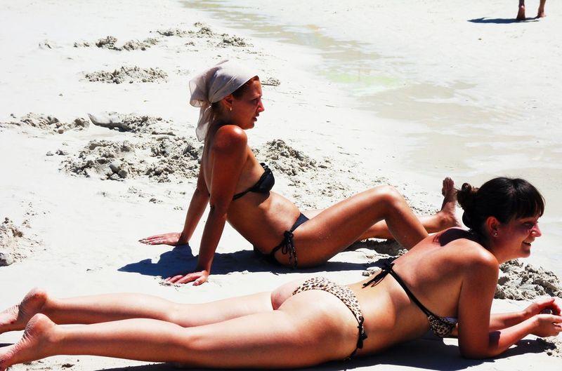 Female friends wearing bikinis while relaxing at beach