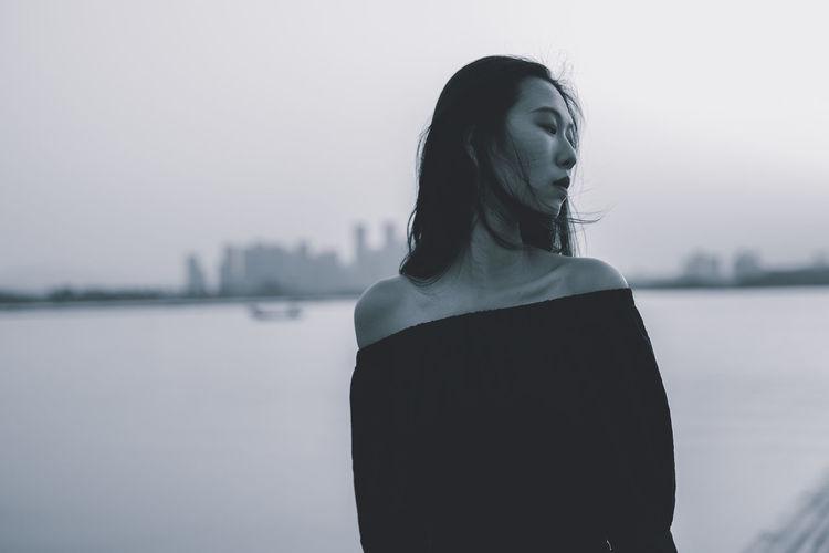 Woman looking at lake against sky