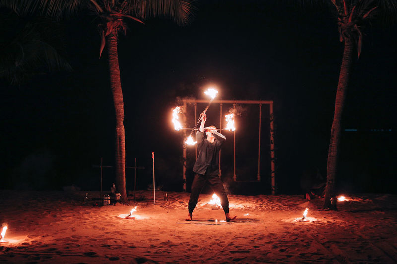 Rear view of man holding illuminated fire at night