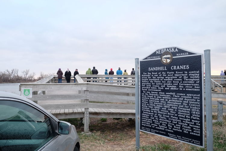 Car Parked By Historical Marker With People On Pier Against Sky