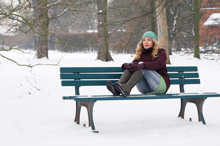 Portrait of blond woman sitting on bench in snow covered park