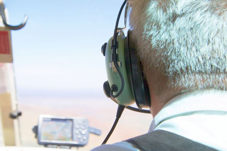 Aerospace Industry Air Vehicle Airplane Close-up Cockpit Flying Headphones Headset One Person Outdoors Pilot Piloting Real People Rear View Sky Technology Transportation