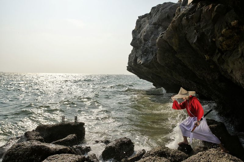 ASIAN WOMAN WITH TRADITIONAL CLOTHING STANDING ON SEASHORE