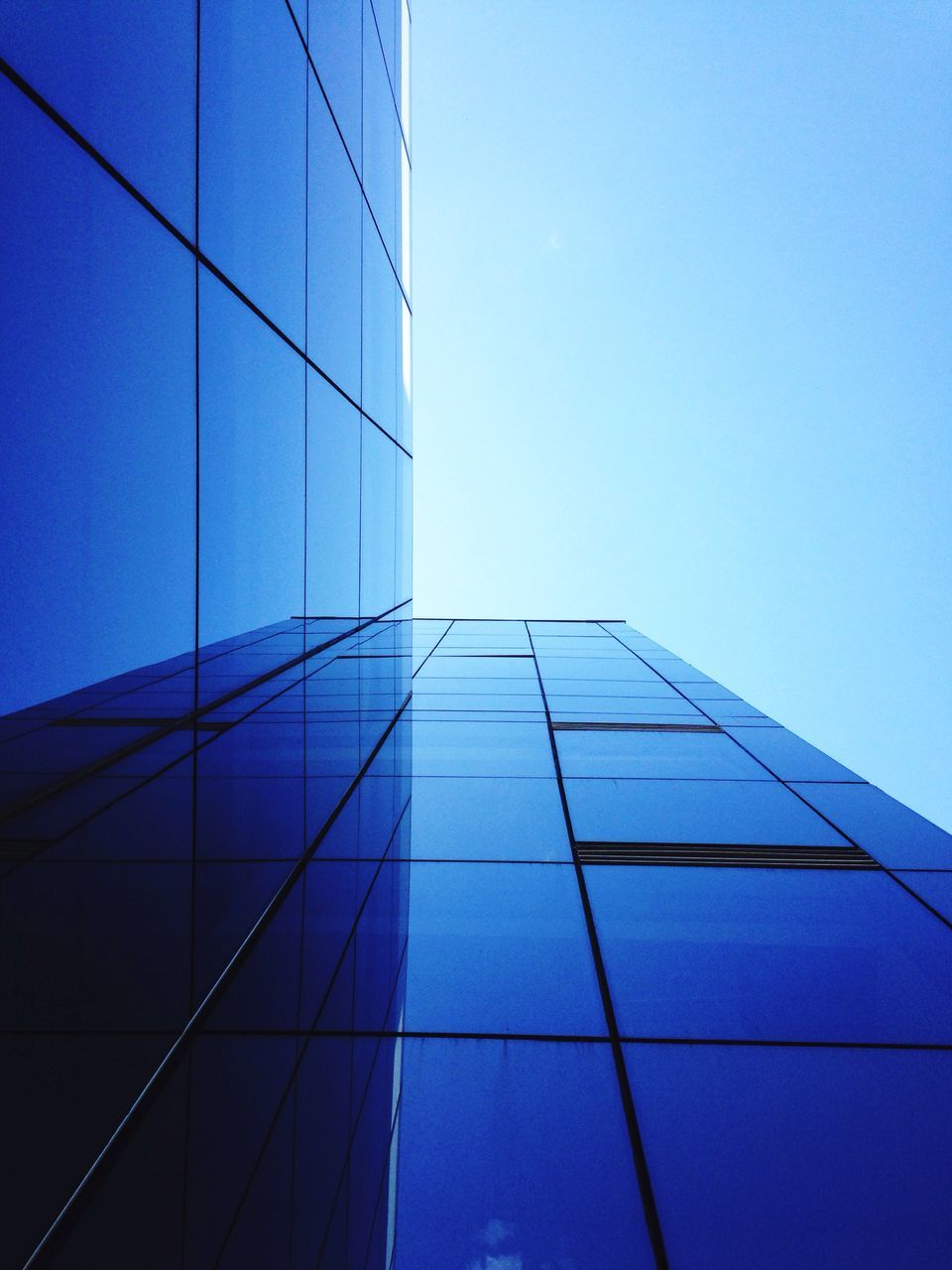 architecture, built structure, building exterior, modern, skyscraper, blue, glass, tall, reflection, growth, low angle view, no people, development, day, city, clear sky, corporate business, outdoors, sky