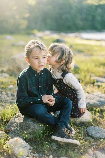 Siblings sitting outdoors