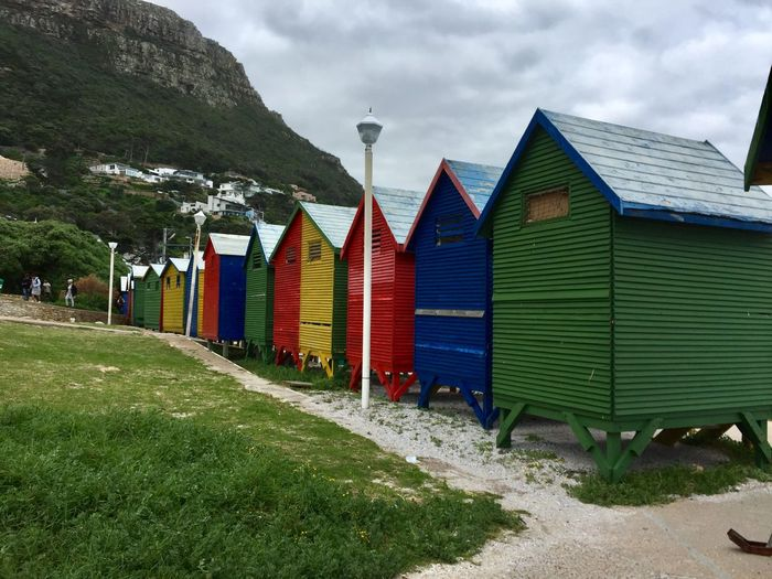 Beach huts by buildings against sky