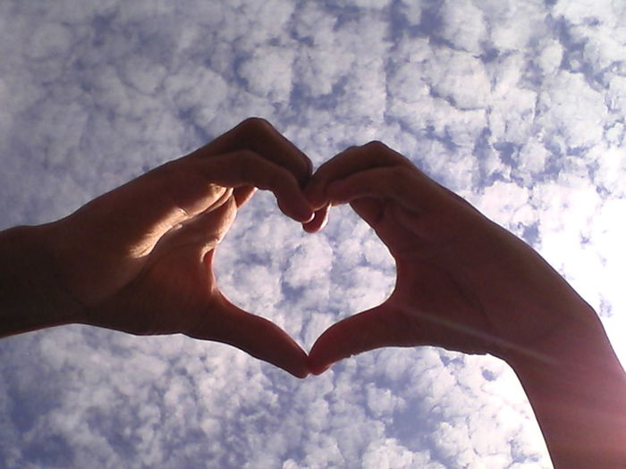 Low angle view of couple making heart shape against cloudy sky