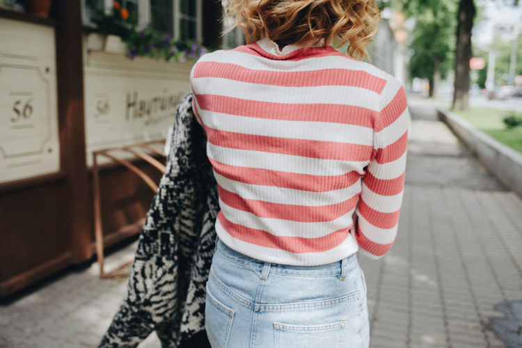 Woman in the street Adult Adults Only Casual Clothing City Close-up Day Leisure Activity Lifestyles One Person Outdoors People Real People Rear View Standing Striped Women Young Adult Young Women