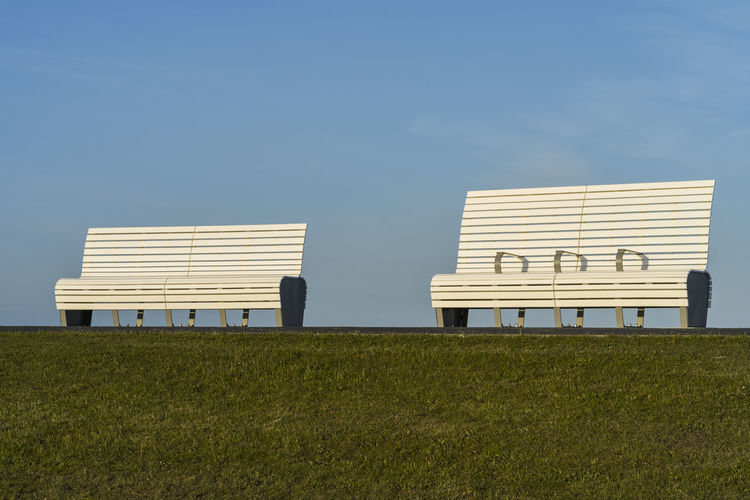 Hooded beach chairs on field against clear sky